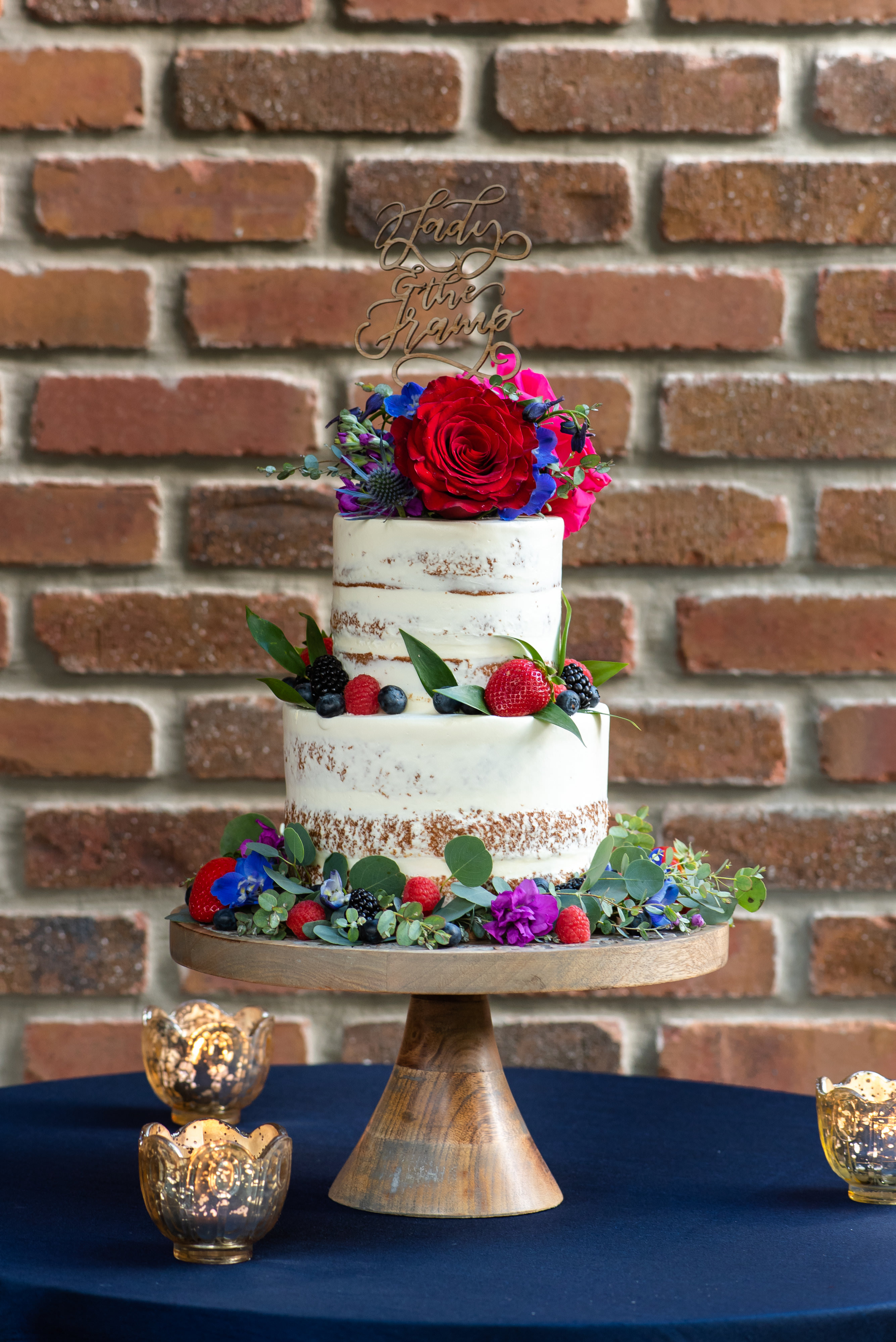 Two Tier Rustic Semi Naked Wedding Cake with Red, Purple, Pink, Blue and Greenery Real Flower Decor, Laser Cut Cake Topper and Red Rose, Pink Floral Cake Topper on Wooden Cake Stand, Blue Tablecloth, Gold Mercury Candles | Tampa Bay Wedding Photographer Caroline and Evan Photography | Florist Monarch Events and Design | Designer and Planner Southern Glam Weddings and Events | Cake Baker Artistic Whisk