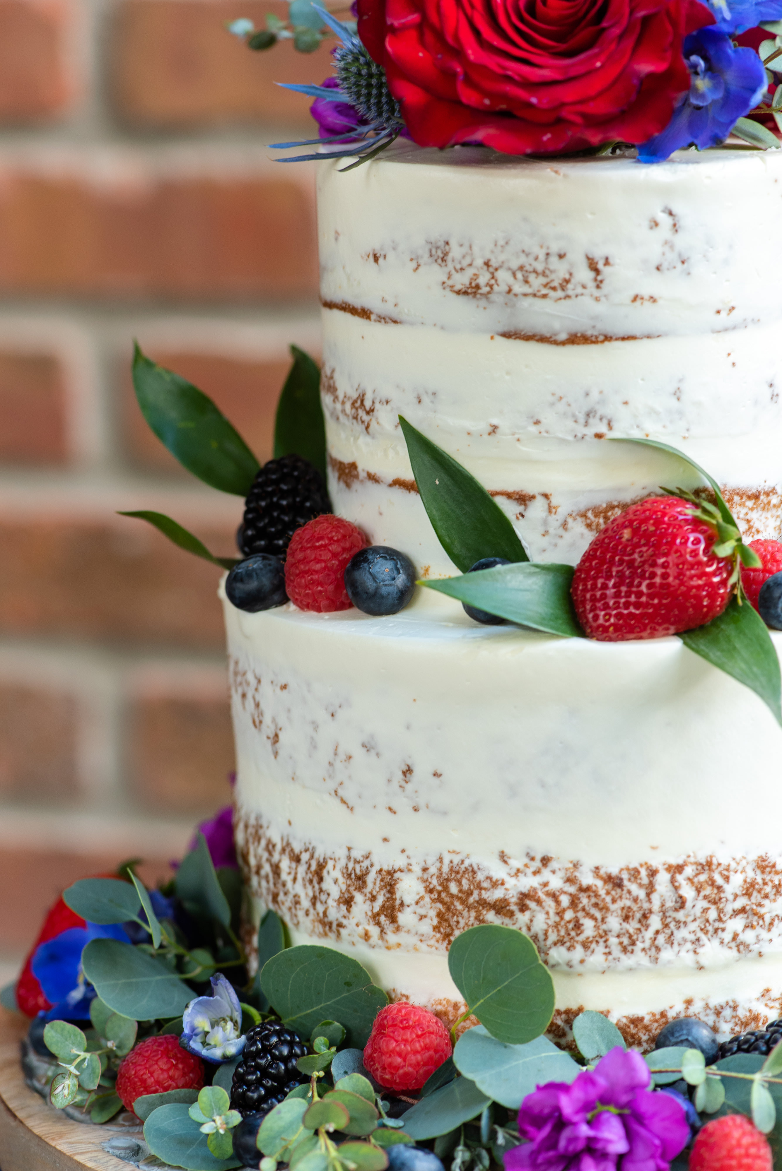 Two Tier Rustic Semi Naked Wedding Cake with Red, Purple, Pink, Blue and Greenery Real Flower Decor | Tampa Bay Wedding Photographer Caroline and Evan Photography | Florist Monarch Events and Design | Designer and Planner Southern Glam Weddings and Events | Cake Baker Artistic Whisk