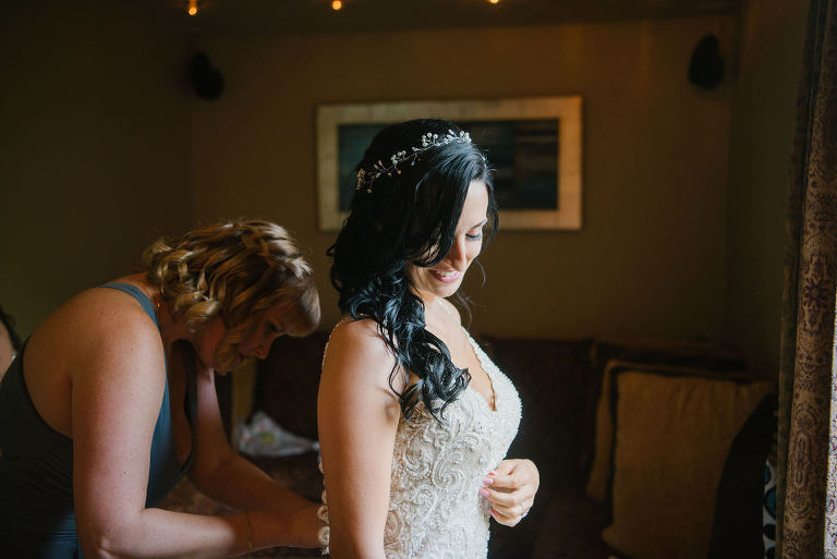 Bride in lace wedding dress getting dresses with crown hairpiece and flowing curls