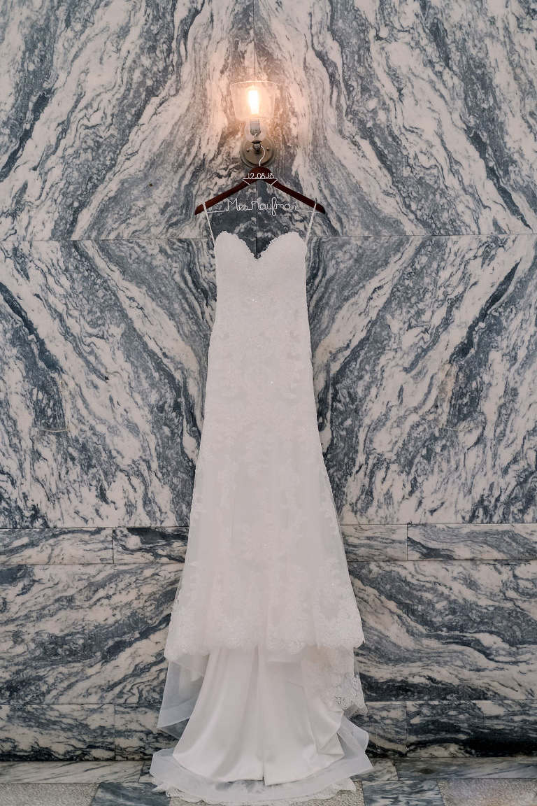 Strapless Sweetheart Lace Fitted Maggie Sottero Wedding Dress on Custom Hanger and Marble Wall Backdrop
