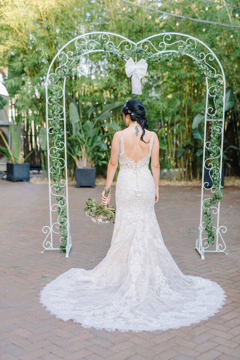Bride in lace wedding dress under metal and greenery arch