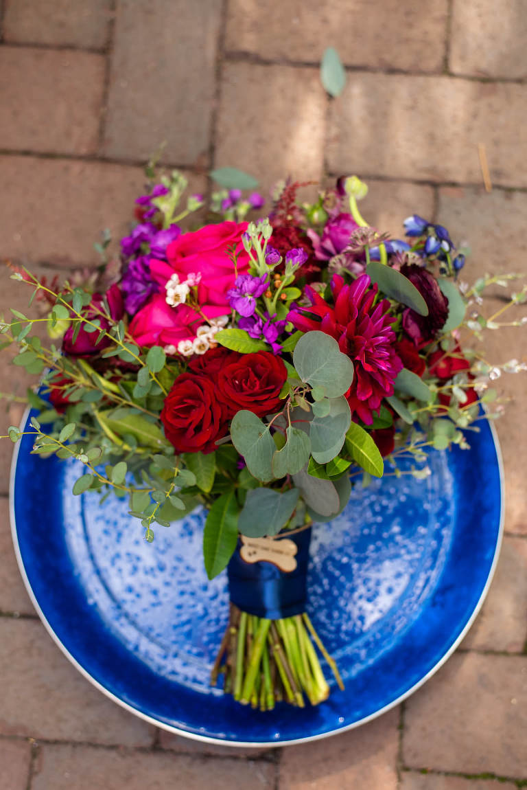 Organic Dark Red, Pink, Purple and Greenery Floral Bouquet with Wooden Dog Bone Brooch and Navy Blue Ribbon | Tampa Bay Wedding Photographer Caroline and Evan Photography | Florist Monarch Events And Design | Designer and Planner Southern Glam Weddings & Events