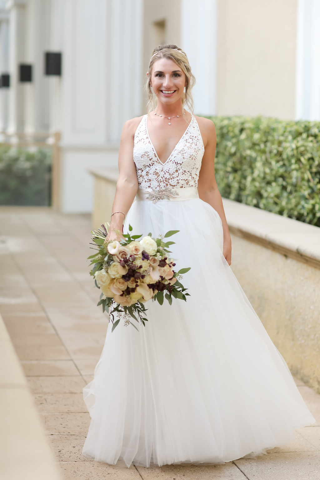 Florida Bride Outdoor Wedding Portrait, Bride in Lace Nude and White Deep V Neckline Bodice with Straps, Ivory Sash with Floral Rhinestone Brooch, Tulle and Illusion Skirt with Organic Ivory, Dark Purple and Greenery Flower Bouquet   Tampa Bay Wedding Photographer Lifelong Photography Studios