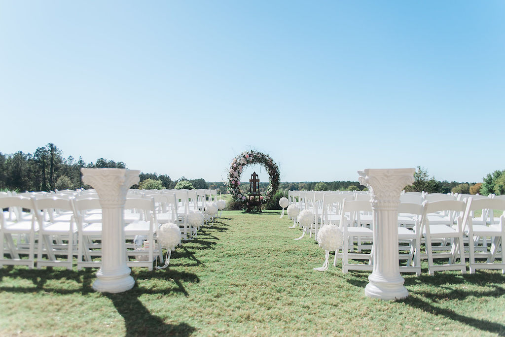 Golf Course Wedding Ceremony Decor, White Folding Chairs, White Pedestals, Circular Wooden Branches Ceremony Arch with Ivory and Blush Pink Flowers | Tampa Bay Wedding Venue Southern Hills Plantation Club