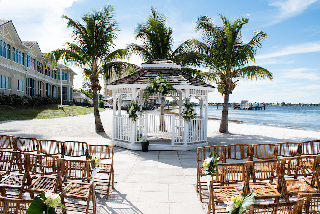 Outdoor Beach Wedding Ceremony at Gazebo with White Florals and Green Palm Tree Branches, Wooden Folding Chairs | Waterfront Venue Isla Del Sol Yacht and Country Club