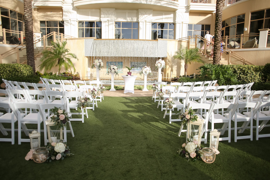 Outdoor Lawn Wedding Ceremony, White Folding Chairs, Ivory, Purple and Greenery Flower Decor, White Tall and Small Lanterns, White Pedestals with Floral Bouquets | Tampa Bay Wedding Photographer Lifelong Photography Studios | Clearwater Beach Wedding Hotel Venue Sandpearl Resort | Wedding Planner Special Events Planning