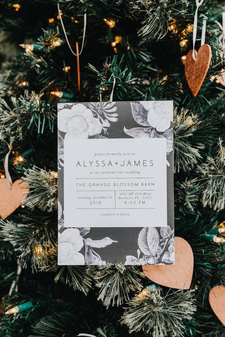 Romantic Black and White Monochromatic Floral Wedding Invitation Against Christmas Tree Backdrop