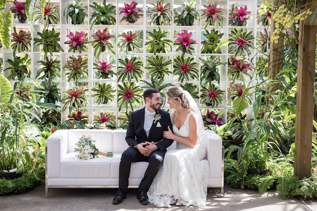 Romantic Bride and Groom Sarasota Garden Wedding Portrait on White Couch with Tropical Flowers and Greenery Backdrop | Sarasota Wedding Venue Marie Selby Botanical Gardens