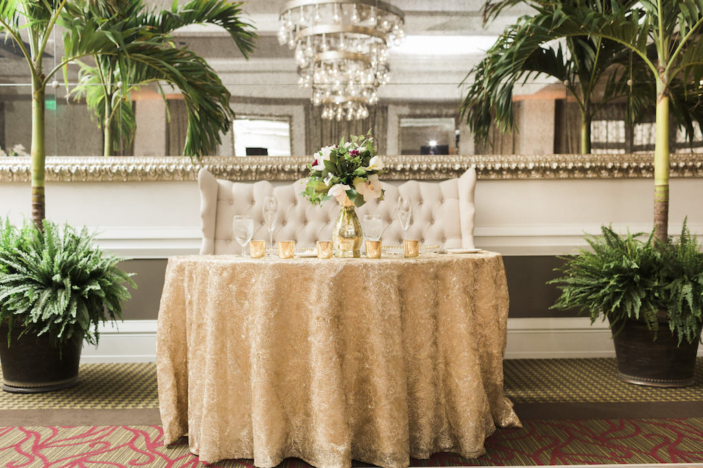 Classic Wedding Reception Decor, Sweetheart Table with Gold Tablecloth, Gold Mercury Candle Votives, Low Gold Tased with Greenery and Ivory Floral Centerpiece, Ivory Tufted Loveseat | Tampa Bay Wedding Planner Love Lee Lane | St. Petersburg Wedding Venue The Birchwood