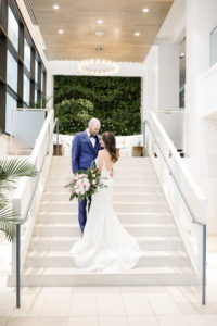 Destination Florida Bride and Groom Wedding Portrait on Hotel Staircase in Courtyard, Groom in Blue Tuxedo, Bride in White and Pink Flower Bouquet with Green Palms, Bride in Spaghetti Strap Backless White Fitted Hayley Paige Wedding Dress | Photographer Lifelong Photography Studios | Hotel Wedding Venue The Hilton Clearwater Beach Resort & Spa