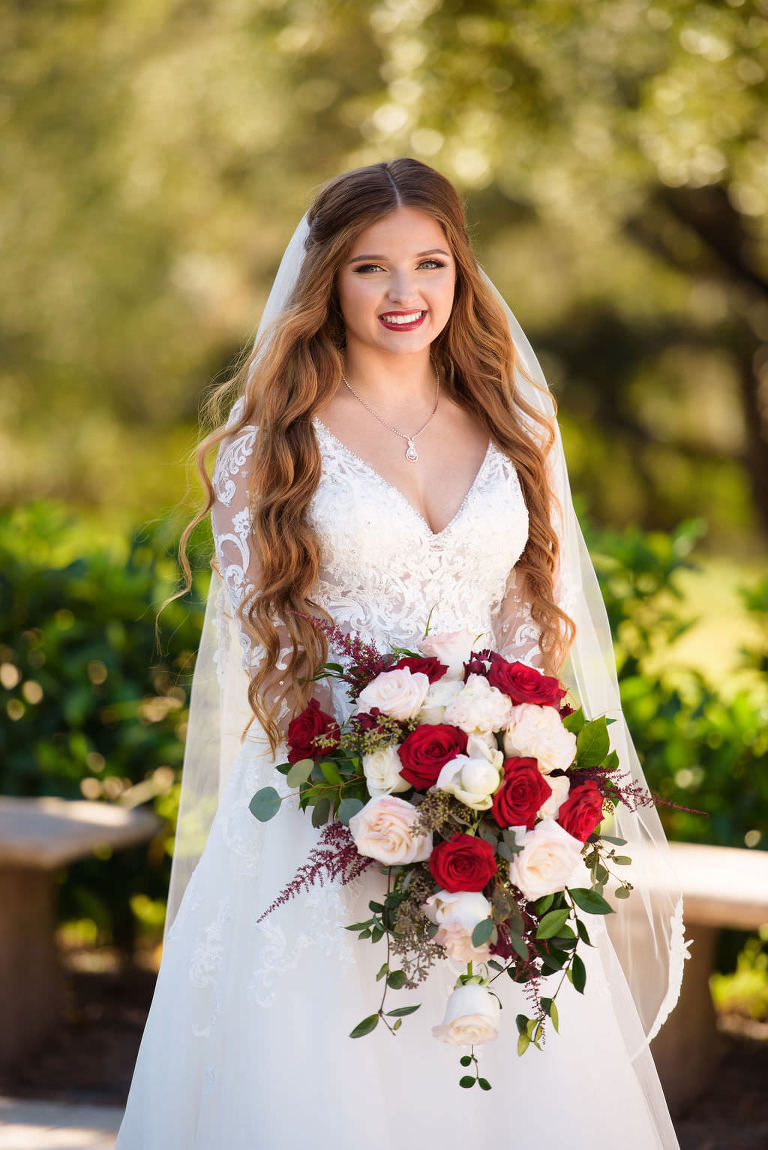 Florida Bride Wedding Portrait in Lace and Illusion Long Sleeve Deep V Neckline Ballgown Wedding Dress and Red, Blush Pink, Ivory, Greenery Floral Bouquet | Tampa Bay Hair and Makeup Destiny and Light Hair and Makeup Group | Wedding Dress Shop Truly Forever Bridal