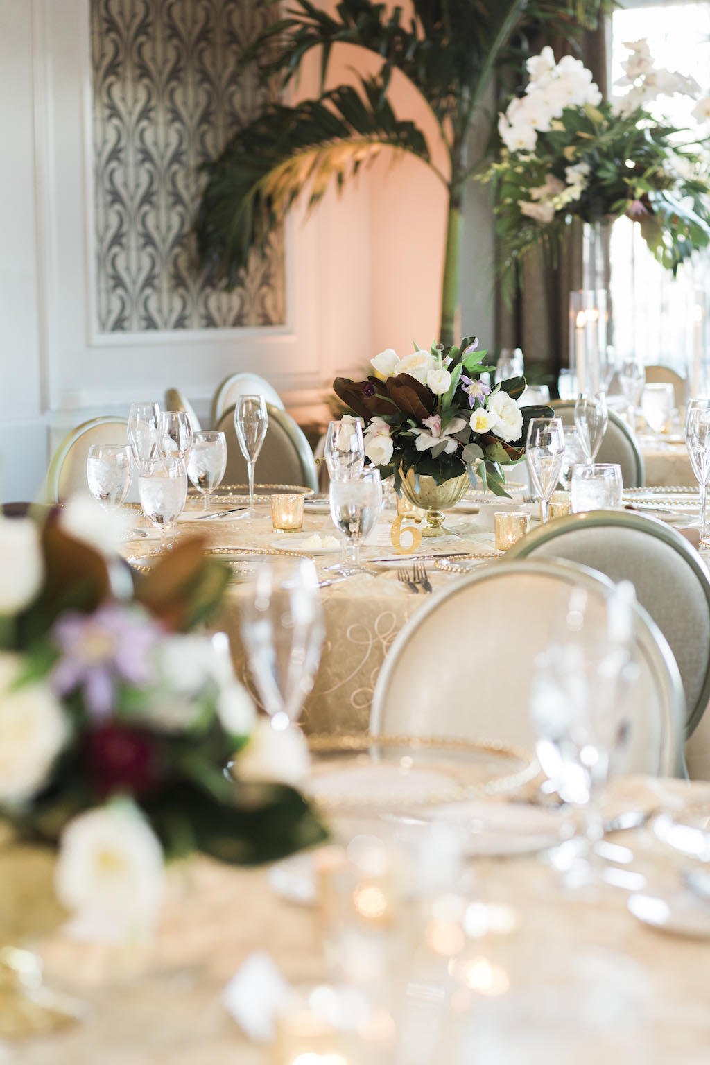 Classic Wedding Reception Decor, Round Tables with Gold Tablecloths, Mix and Match Low and Tall White, Dark Purple, Greenery Floral Centerpieces in Gold Vases