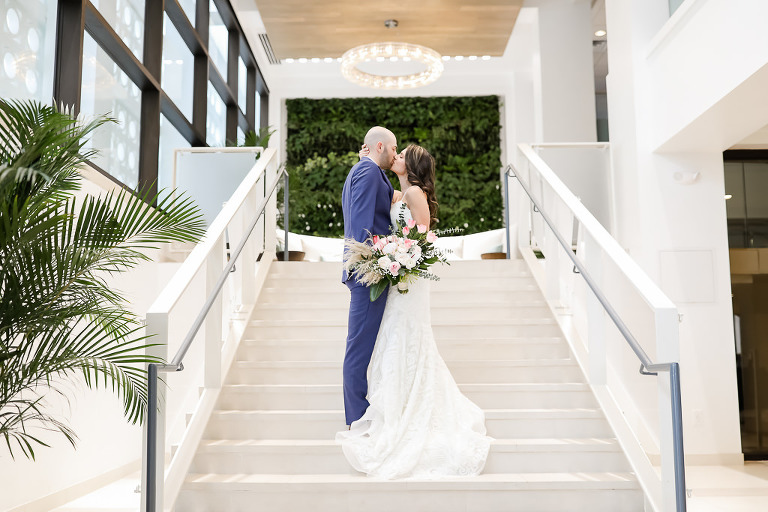 Florida Bride and Groom Intimate Wedding Portrait on Hotel Staircase in Courtyard, Groom in Blue Tuxedo, Bride in White and Pink Flower Bouquet with Green Palms, Bride in Spaghetti Strap White Fitted Hayley Paige Wedding Dress | Photographer Lifelong Photography Studios | Hotel Wedding Venue The Hilton Clearwater Beach Resort & Spa