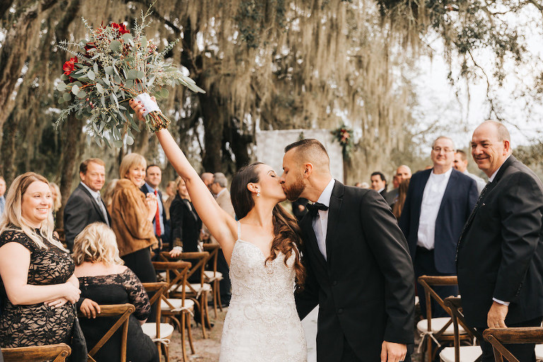 73e09d7e3b73 Bride and Groom Intimate Wedding Portrait, Kissing During Wedding  Recessional While Holding Red and Green. Tampa Bay ...