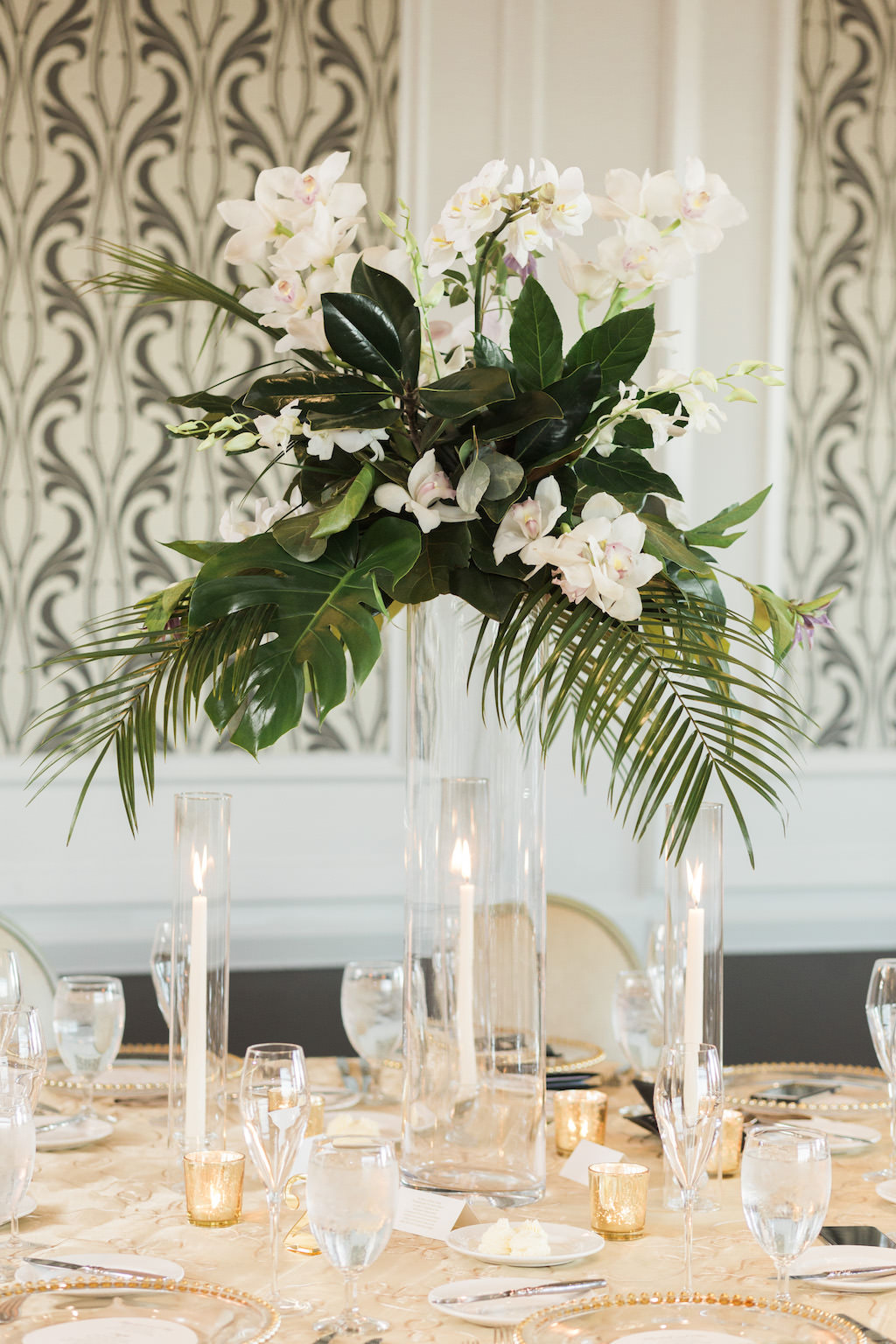 Classic, Tropical Inspired Wedding Reception Decor, Tall Glass Cylinder Vase with Palm Tree Branches, White Orchids and Green Leaves Floral Centerpiece, Round Table with Gold Tablecloth, Tall Candlesticks in Clear Cylinder Vases