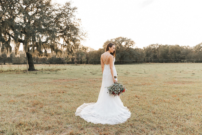Tampa Bay Bride Wedding Portrait, Crisscross White Backless Wedding Dress Holding Green and Red Wedding Bouquet | Rustic Wedding Venue The Orange Blossom Barn | Wedding Dress Shop Truly Forever Bridal