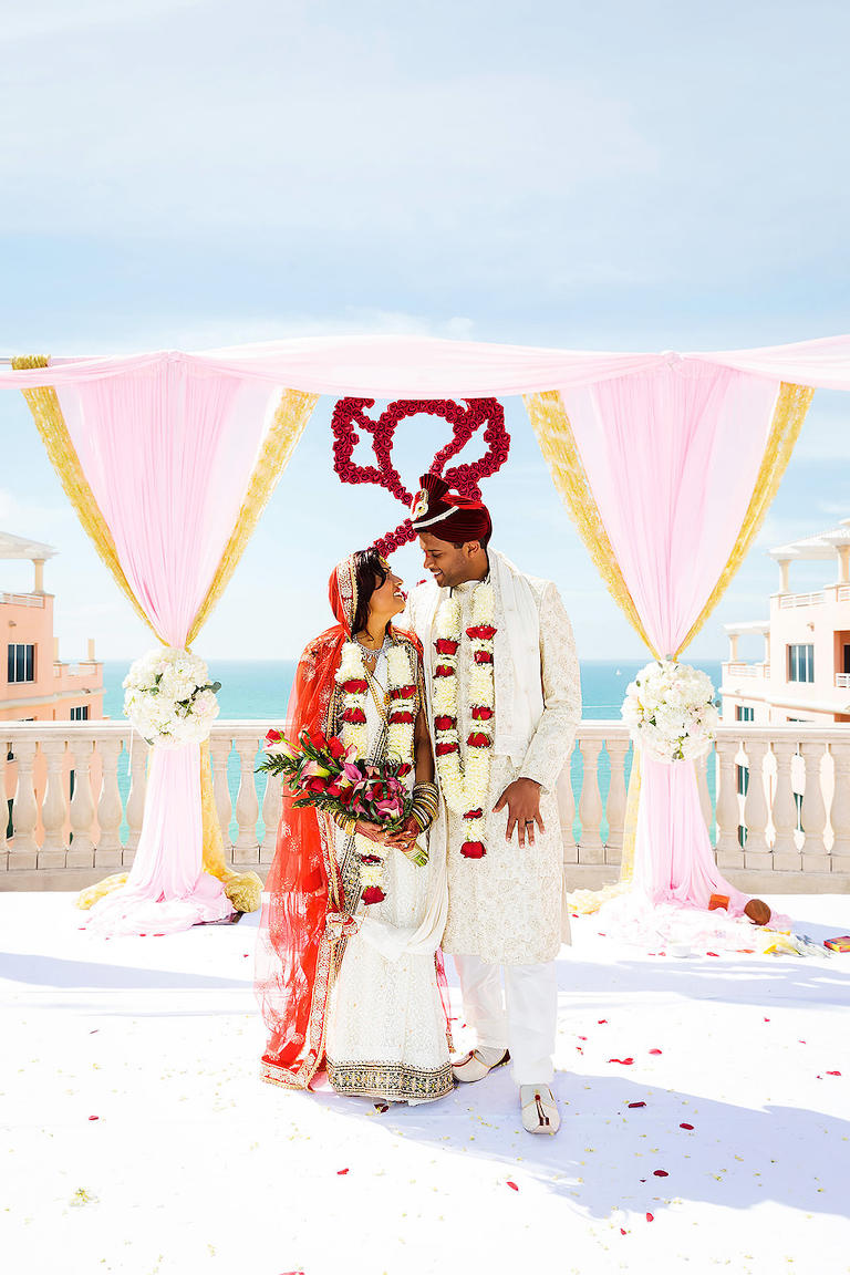 Florida Indian Bride and Groom Wedding Ceremony Portrait, Blush Pink and Gold Linen Drapery Arch, White and Blush Pink Floral Bouquets, Bride Wearing White Saree and Red Headdress, Groom Wearing White Dress Suit and Red and White Floral Leis | Clearwater Beach Waterfront Wedding Venue Hyatt Regency Clearwater Beach