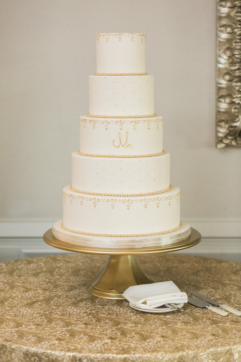 Classic Five Tier White Wedding Cake with Gold Embellishments on Round Table with Gold Tablecloth and Monogram Initials