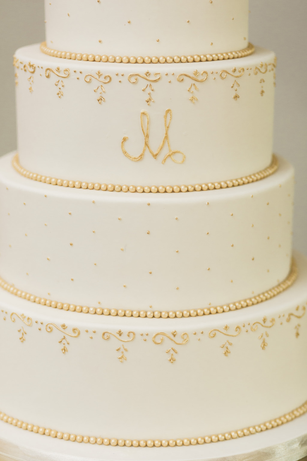 Tiered Classic White Wedding Cake with Gold Dots, Gold Pearls, Gold Embellishments and Gold Letter Monogram Initials