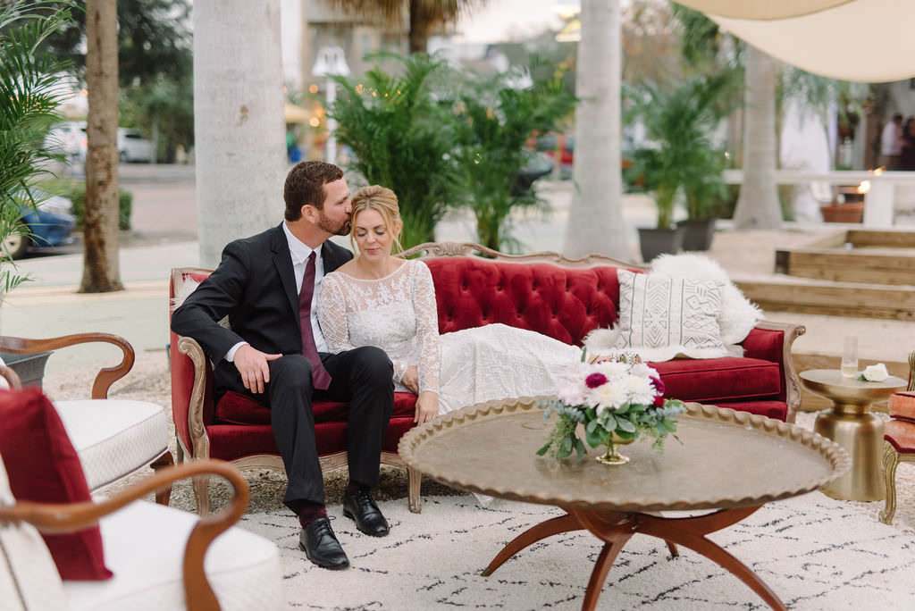 Bride and Groom Wedding Portrait Reclining on Vintage Velvet Couch | Outdoor Wedding Reception Seating Area with Vintage Arm Chairs and Velvet Sofa | Outdoor St. Pete Wedding Reception Venue Intermezzo | St. Pete Wedding Photographer Kera Photography