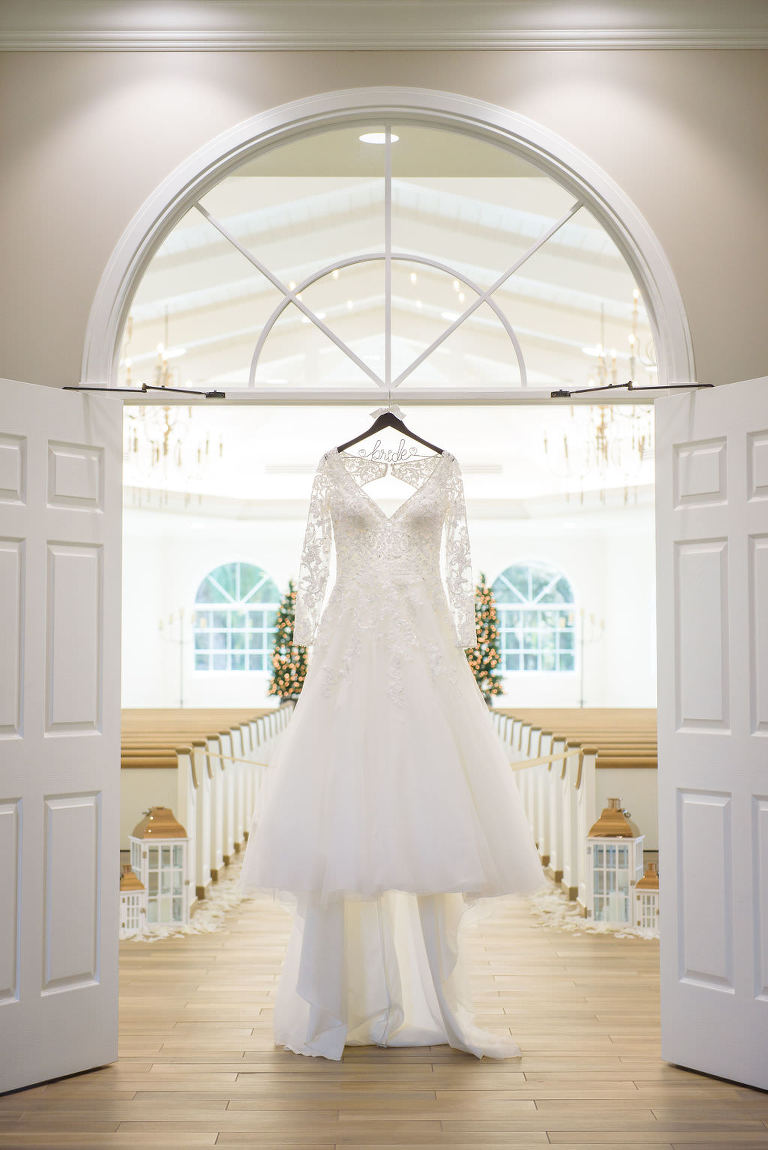 Lace and Illusion Long Sleeve Deep V Neckline Ballgown Wedding Dress Hanging in Wedding Chapel Entrance | Safety Harbor Wedding Ceremony Venue Harborside Chapel | Tampa Bay Wedding Dress Shop Truly Forever Bridal