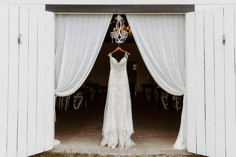Vintage Lace Spaghetti Strap Sweetheart Neckline Lace Fitted Wedding Dress on Wooden Hanger, Against Barn Door, Lace Draping and White Chandelier Backdrop | Tampa Bay Wedding Dress Shop Truly Forever Bridal