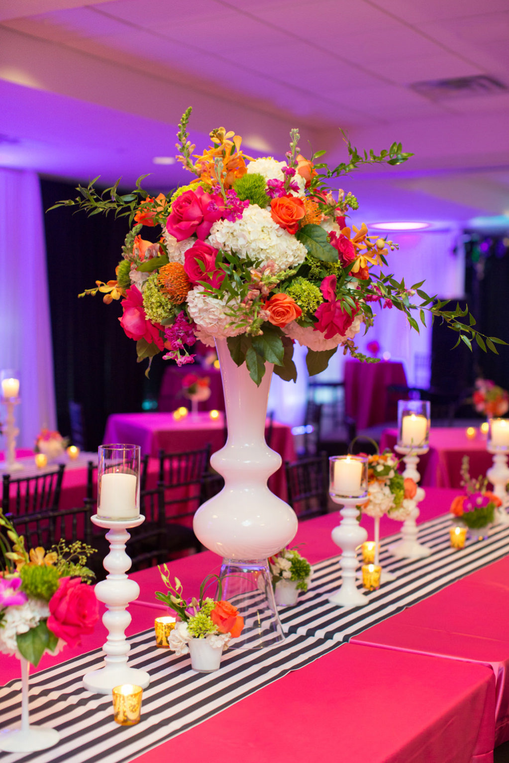 Whimsical Kate Spade Inspired Wedding Reception Decor, Long Table with Hot Pink Tablecloth, Black and White Stripe Table Runner, Tall White Vase with Colorful Pink, Orange, Yellow, White and Green Flower Centerpiece, White Candlesticks | Tampa Bay Wedding Planner Parties A La Carte