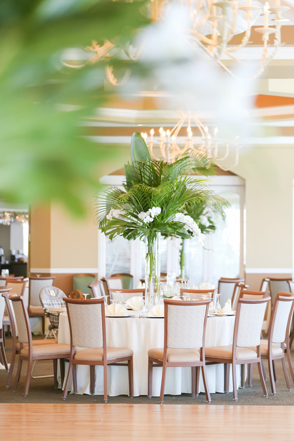 Tropical, Florida Beach Elegant Inspired Ballroom Wedding Reception Decor, Round Tables with Tall Glass Vase, White Florals and Palm Leaf Centerpiece | Photographer LifeLong Photography Studios | St. Pete Beach Waterfront Wedding Venue Isla Del Sol Yacht and Country Club
