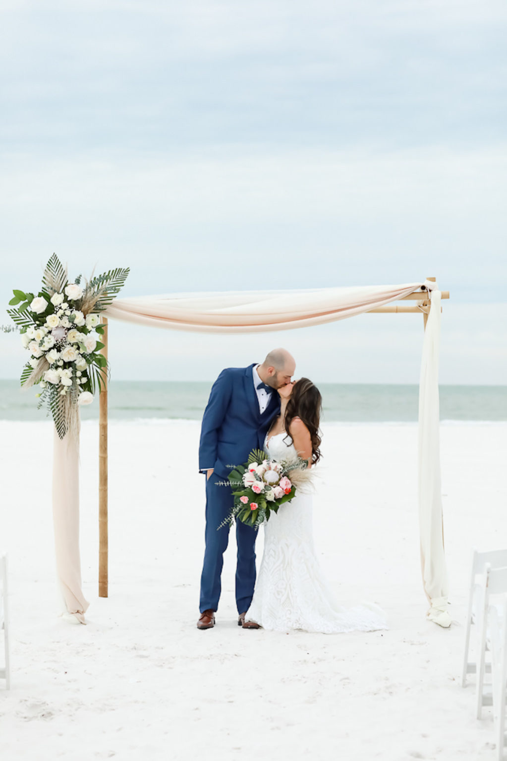 Bride and Groom Intimate Wedding Portrait on the Beach, Bamboo Bamboo Ceremony Arch with Tropical Inspired Floral Arrangement | Photographer Lifelong Photography Studios | Hilton Clearwater Beach