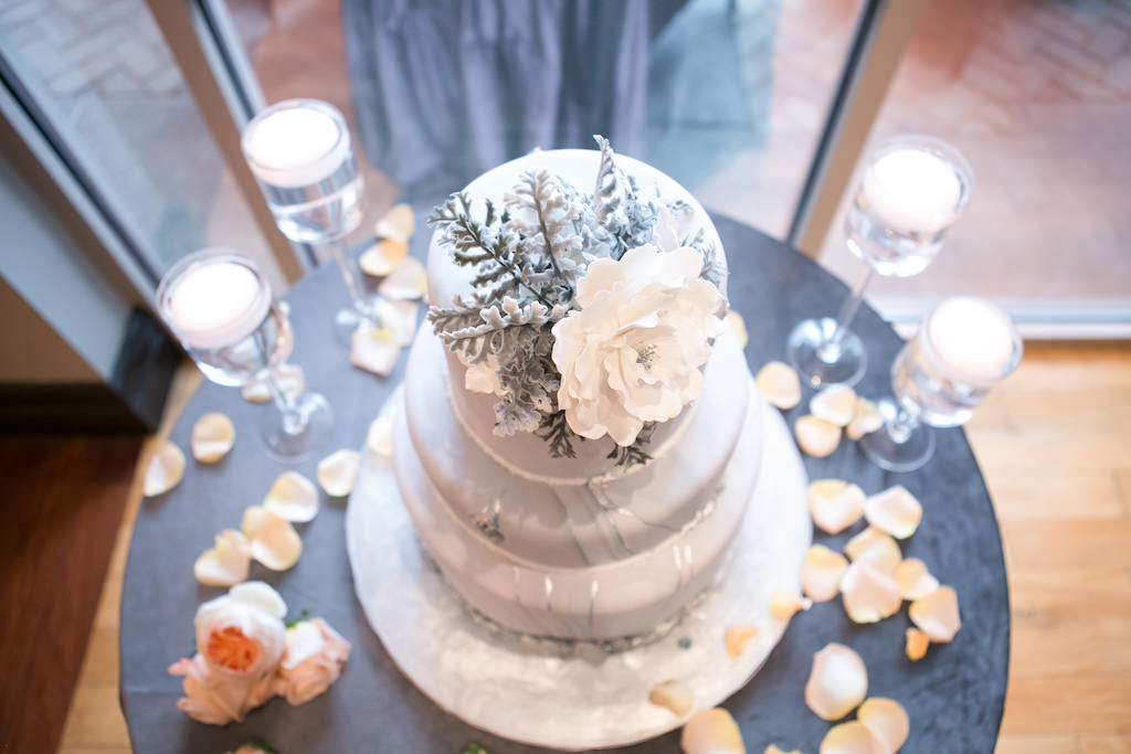 Three Tier Marble Wedding Cake with Silver Accents and White Sugar Flower Cake Topper on Round Table with Dusty Blue Tablecloth | Tampa Bay Photographer Carrie Wildes Photography | Linen Rental Gabro Event Services | Wedding Cake Alessi Bakeries