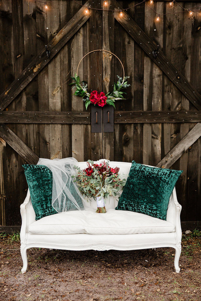 Rustic Christmas Inspired Wedding Decor, Wooden Barn Backdrop with White Vintage Loveseat with Green Pillows and Wedding Veil, Wedding Bouquet with Red Florals and Greenery, Hanging Gold Floral Hoop with Red Roses | Bushnell Florida