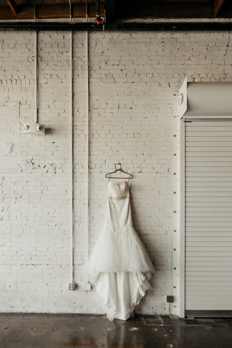 Lace Sweetheart Strapless Fitted Bodice with Rhinestone Belt, Tulle Full Skirt Wedding Dress Hanging on Hanger and White Brick Wall Backdrop | Lakeland Industrial Modern Wedding Venue and Event Space Haus 820
