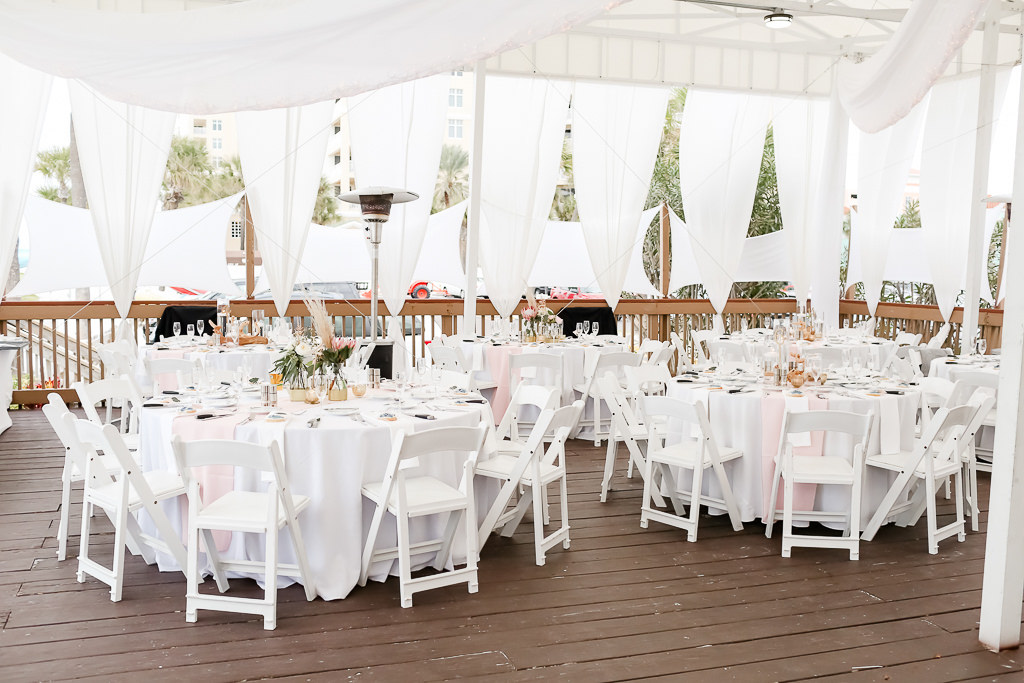 Outdoor Beach Deck Wedding Reception Decor Round Tables White Table Cloths White Folding Chairs Blush Runners White Linen Drapery Low Centerpieces Photographer Lifelong Photography Studios Hotel Wedding Venue The Hilton