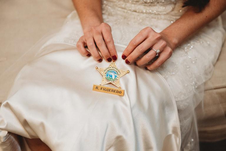 Tampa Bay Bridal Portrait Holding Spouse's Hillsborough Country Sheriff Department Law Enforcement Badge on Wedding Dress