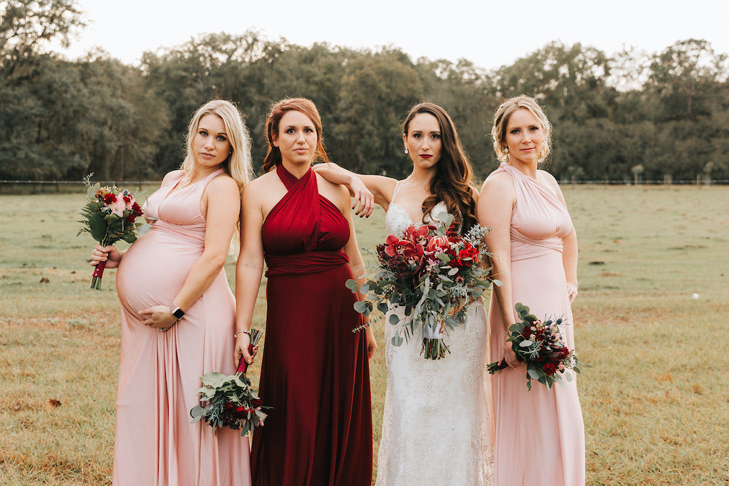 Tampa Bay Rustic Bride and Bridesmaid Wedding Portrait, Bridesmaids in Red and Blush Pink Long Mismatched LuLus Bridesmaid Dresses, Carrying Red and Pink Floral Bouquet With Greenery, Against Rustic Rural Backdrop