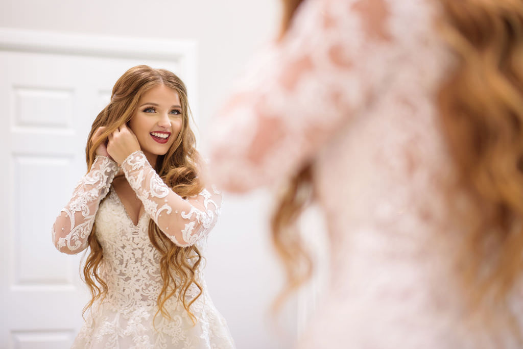 Florida Bride Getting Ready Wedding Portrait in Lace and Illusion Long Sleeve Deep V Neckline Ballgown Wedding Dress | Tampa Bay Hair and Makeup Destiny and Light Hair and Makeup Group | Wedding Dress Shop Truly Forever Bridal
