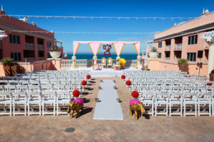 Florida Indian Hindu Rooftop Wedding Ceremony Decor, Gold Elephant Statues, White Folding Chairs, Red Floral Pom Poms, Pink and Gold Linen Drapery Arch, White Aisle Runner and String Lights | Clearwater Beach Waterfront Wedding Venue Hyatt Regency Clearwater