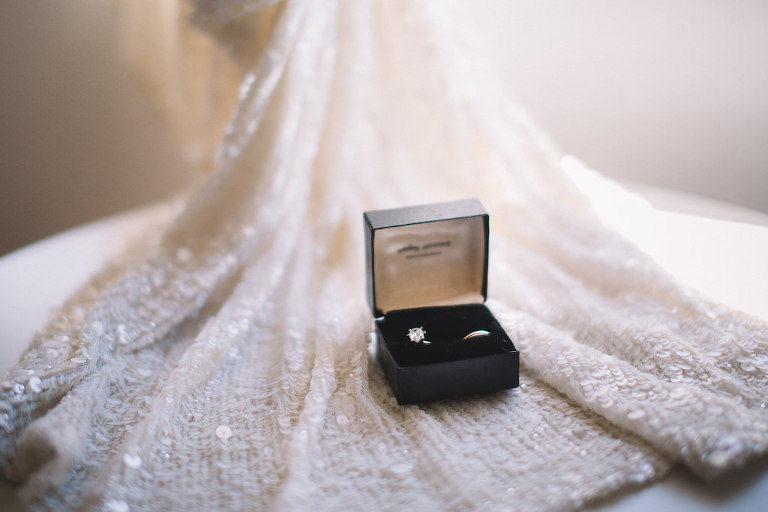 Solitaire Diamond Engagement Ring and Wedding Band in Ring Box, on top of White Sequined Runner