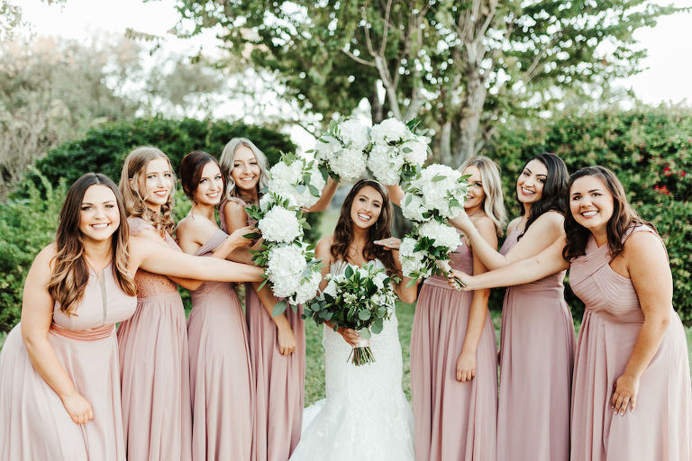 Florida Garden Bride and Bridesmaids Wedding Portrait, Bride in White Fit and Flare Wedding Dress, Bridesmaids in Mix and Match Long Mauve Dresses, Carrying White Floral Bouquet with Baby's Breath and Greenery | Tampa Bay Florist Monarch Events and Design