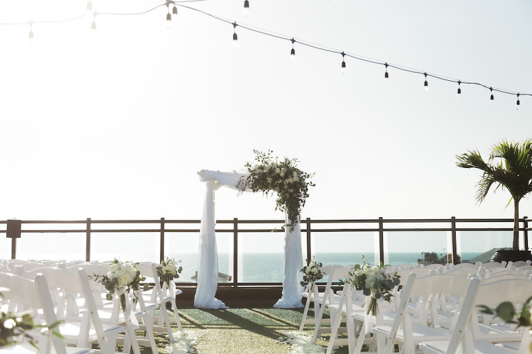 Rustic, Romantic, Beach Inspired Rooftop Waterfront Wedding Ceremony Decor , White Folding Chairs with Floral Bouquets, Arch with White Linen Drapery and Organic Ivory, Greenery Floral Arrangement | St. Pete Beach Wedding Venue Hotel Zamora