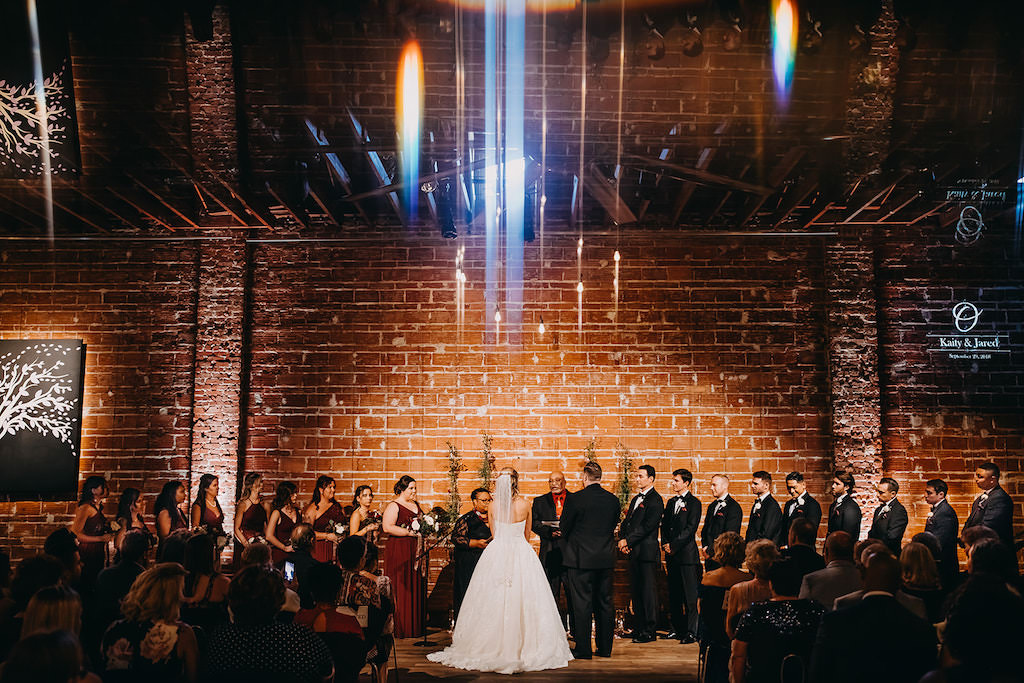 Bride and Groom with Wedding Party at the Altar During Wedding Ceremony in Front of Red Brick Exposed Wall, Ceremony Portrait with LensFlair, Bride Wearing Strapless White Ballgown with Veil, Bridesmaids in Burgundy Wine Maroon Long Dresses, Groom Wearing Classic Black Tux and Tie, Groomsmen in Black Tuxedo and Black Bowtie with Red Pocket Square   Downtown St. Pete Wedding Venue NOVA 535