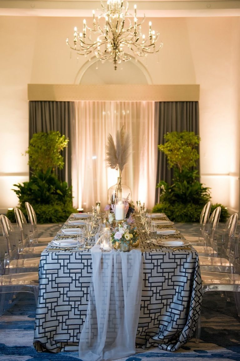 Chic Bohemian Inspired Wedding Decor, Long Rectangle Reception Tables with Blue Geometric Linen and White Sheer Runner, Neutral Tone Low Floral Centerpiece, Pampas Grass in Large Clear Glass Jar, Against Hotel Ballroom Backdrop with Greenery and Chandelier Lighting | Tampa Bay Wedding Photographer Andi Diamond Photography | St. Pete Beach Wedding Venue The Don Cesar | Tampa Wedding Rentals A Chair Affair | Tampa Bay Wedding Planner UNIQUE Weddings + Events | Linen Rentals Over the Top Linens