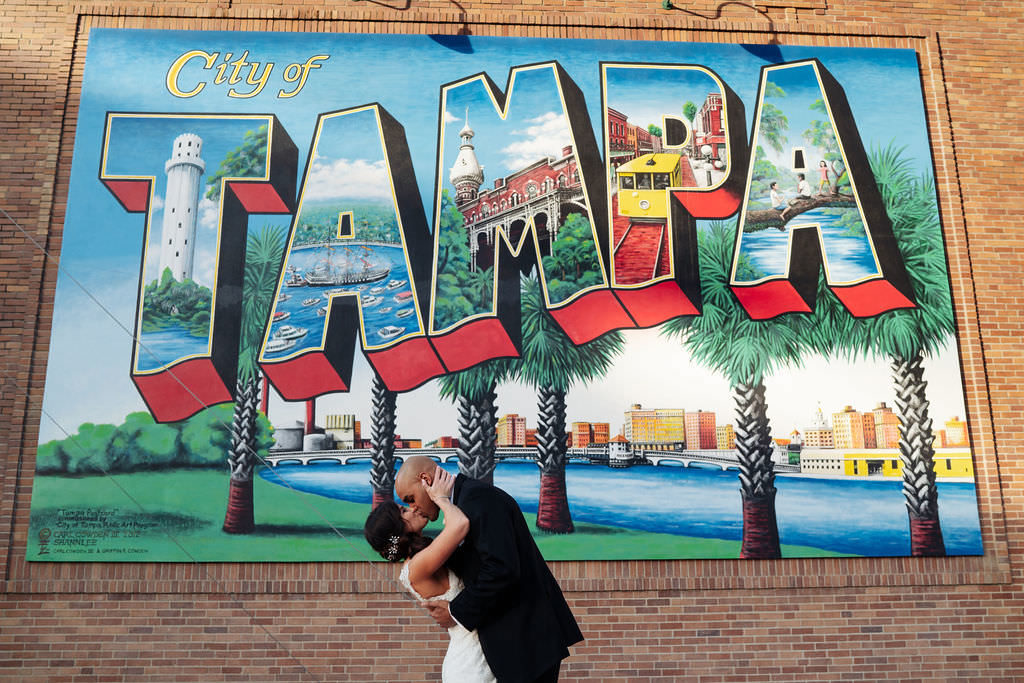 Florida Bride and Groom Wedding Portrait, Kissing In Front of Iconic City of Tampa Art Mural | Tampa Bay Wedding Photographer Grind & Press Photography