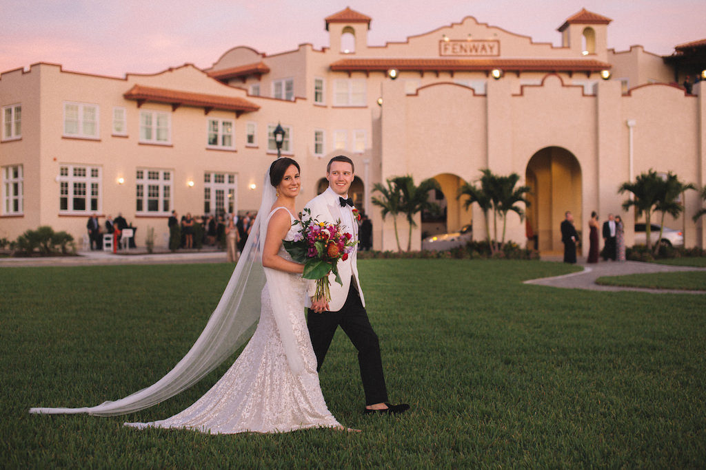 Tampa Bay Bride and Groom Wedding Portrait Outside Boutique Dunedin Hotel Wedding Venue Fenway Hotel, Bride in Sleeveless White Sequin Sheath Wedding Dress with Long Tulle Veil, Carrying Tropical Inspired Wedding Bouquet with Colorful Florals and Greenery