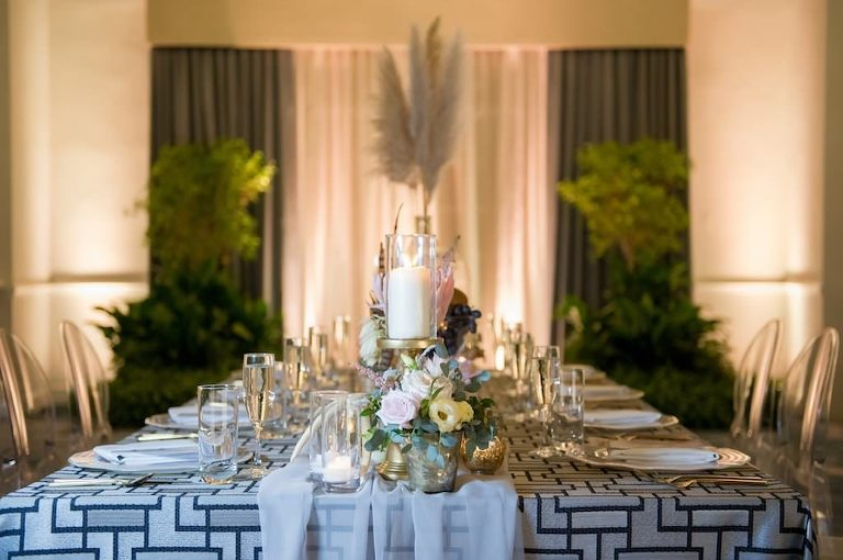 Bohemian Chic Inspired Wedding Decor, Long Rectangle Reception Tables with Blue Geometric Linen and White Sheer Runner, Neutral Tones Low Floral Centerpieces with White Ivory and Pink Roses, King Protea, Thistle, Lisianthus, Antlers, Feathers, Scabiosa, Mercury Glass Votive Candle Holder, Crystal Champagne Flutes, Pampas Grass in Large Clear Glass Jar, Against Hotel Ballroom Backdrop with Greenery and Chandelier Lighting | Tampa Bay Wedding Photographer Andi Diamond Photography | St. Pete Beach Wedding Venue The Don Cesar | Tampa Bay Wedding Planner UNIQUE Weddings + Events | Linen Rentals Over the Top Linens | Rentals A Chair Affair