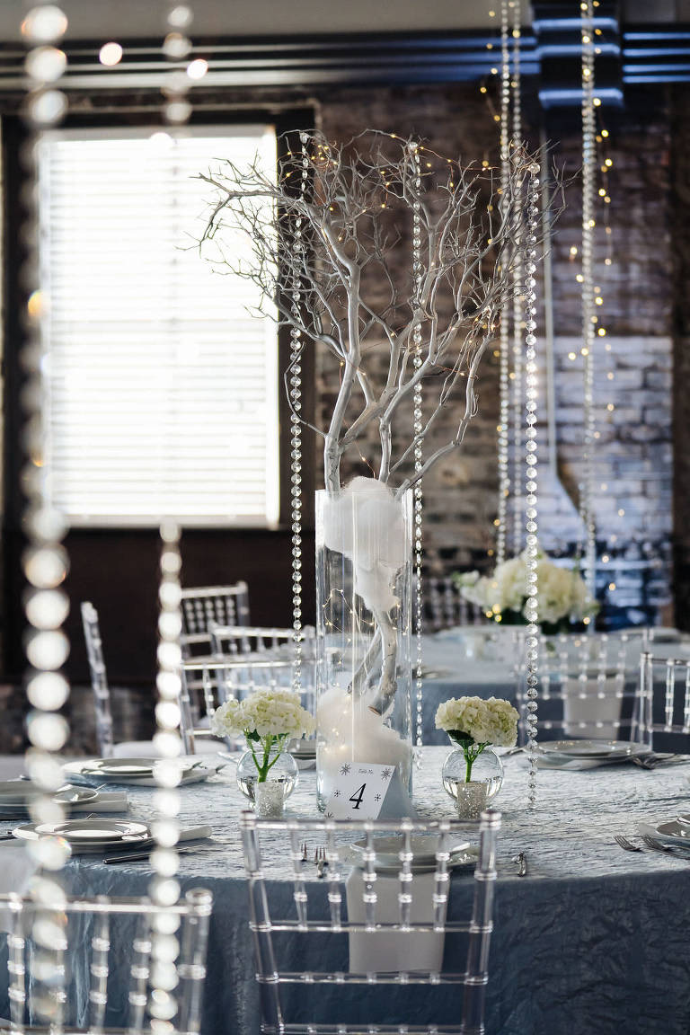 Winter Wonderland Wedding Decor and Reception at Downtown Tampa Wedding Venue, Round Tables with Dusty Blue Tablecloths and Ghost Acrylic Chiavari Chairs, White Small Tree Centerpieces, Crystals, and Candlelights, Low White Floral Arrangement, String Lights, and Table Number | Photographer Grind & Press Photography | Tampa Bay Wedding Planner Special Moments Event Planning | Rentals Gabro Event Services
