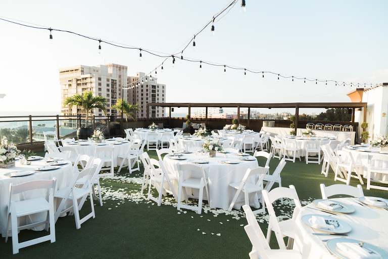 Rustic, Romantic Beach Inspired Rooftop Waterfront Wedding Reception Decor, Round Tables with White Tablecloths, White Folding Chairs, Hanging Bistro Lights, and Low Floral Centerpieces | St. Pete Beach Wedding Venue Hotel Zamora