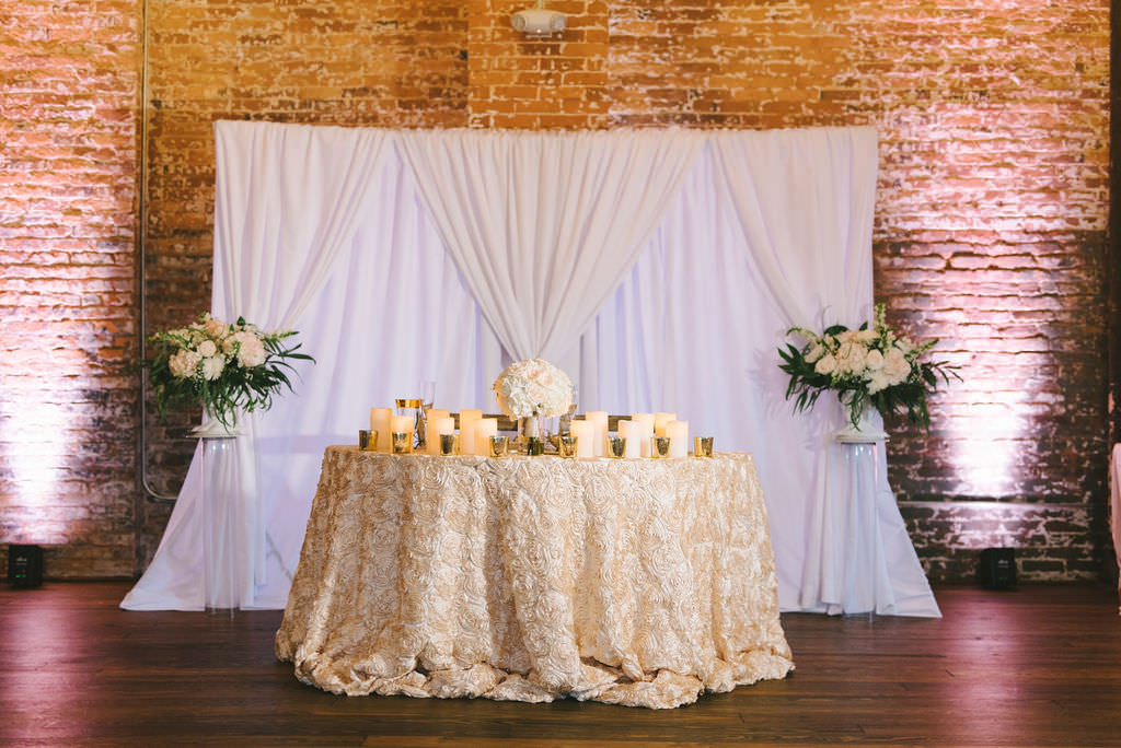 Classic Romantic Wedding Reception Decor, Sweetheart Table with Ivory Floral Linen, Candlesticks, Floral Bouquet Centerpiece, White Drapery and Brick Wall Backdrop, Greenery, Ivory, White Floral Bouquets on Clear Glass Pedestals   Photographer Kera Photography   Tampa Heights Industrial Wedding Venue Armature Works   Planner Kelly Kennedy Weddings and Events
