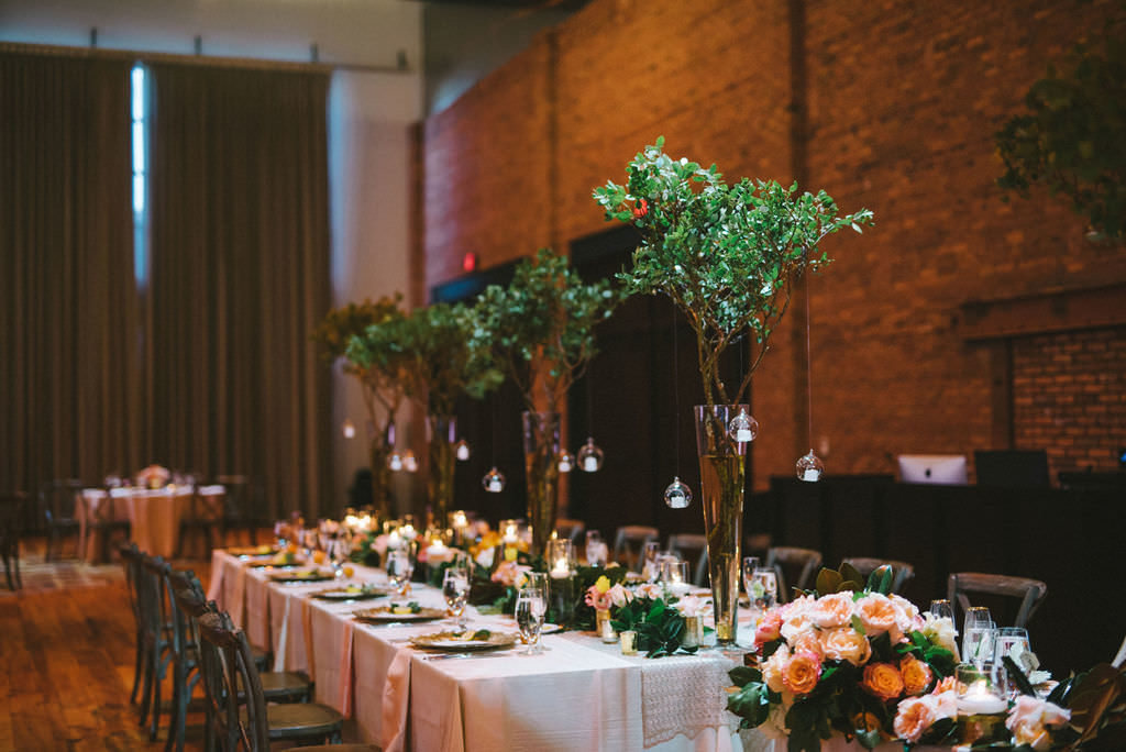 Florida Inspired Wedding Reception Decor, Long Tables with Greenery Garland and Oranges, Wood Chiavari Chairs, Tall Glass Vases with Green Trees and Hanging Glass Cylinder Candles | Tampa Bay Wedding Photographer Kera Photography | Industrial Unique Wedding Venue Armature Works | Wedding Planner Burlap to Lace