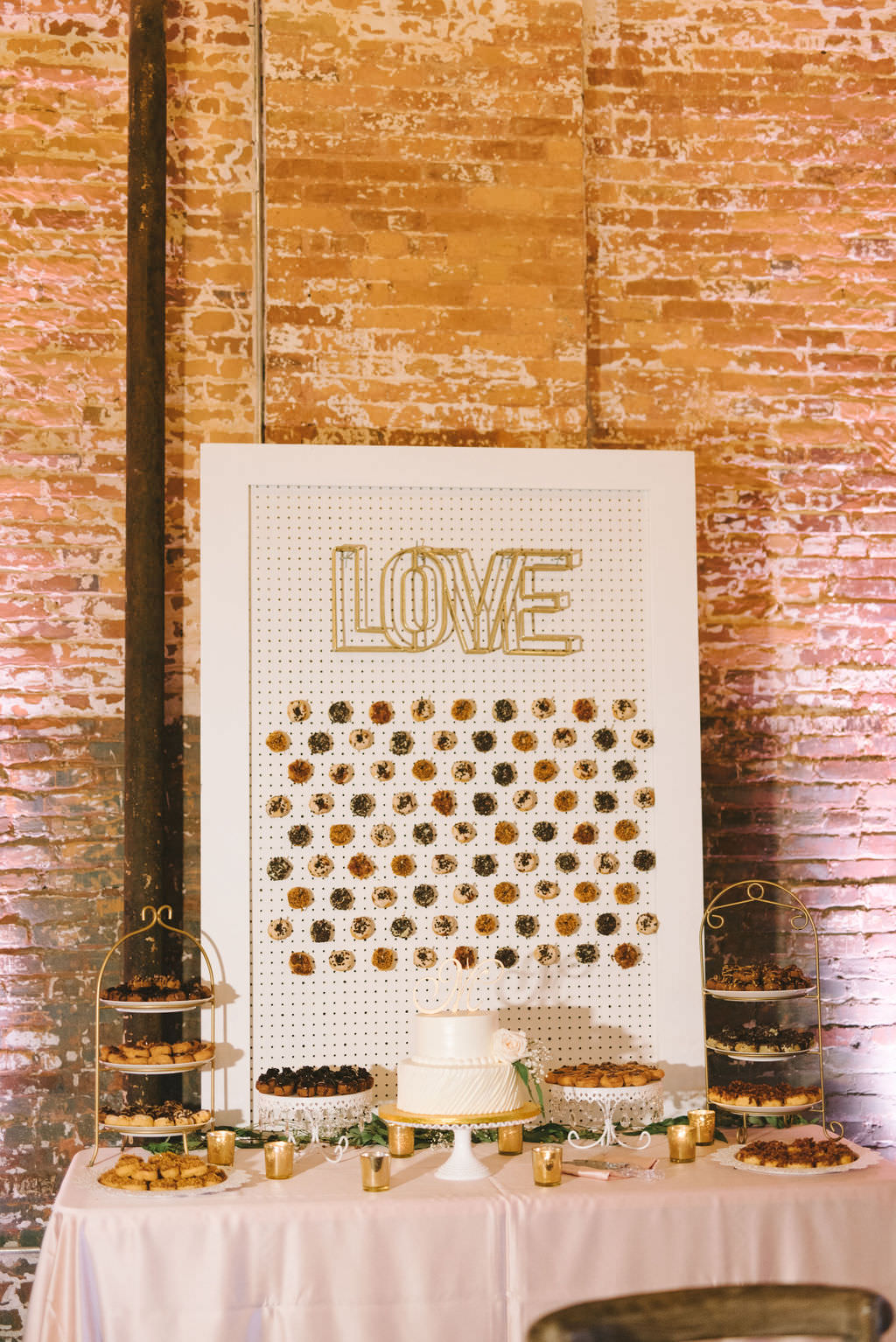 Fun Wedding Dessert Table with Blush Pink Linen, White Display Board with Mini Donut Wall, Gold Love Sign, Two Tier White Wedding Cake   Photographer Kera Photography   Tampa Industrial Wedding Venue Armature Works   Planner Kelly Kennedy Weddings and Events